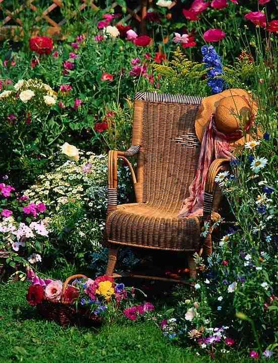 Wiklinowy fotel ogrodowy, kolorowe kwiaty w ogrodzie