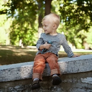 Little blond boy sits on a stone bridge in Tower Grove Park, best location for outdoor family photos.