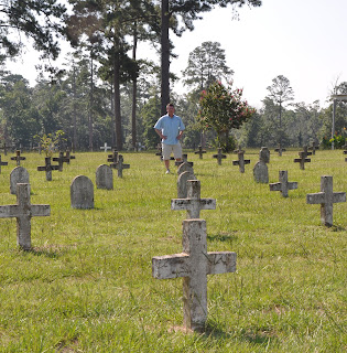 Dr. Frank Wilson stands among the headstones at the Captain Joe Byrd Cemetery.