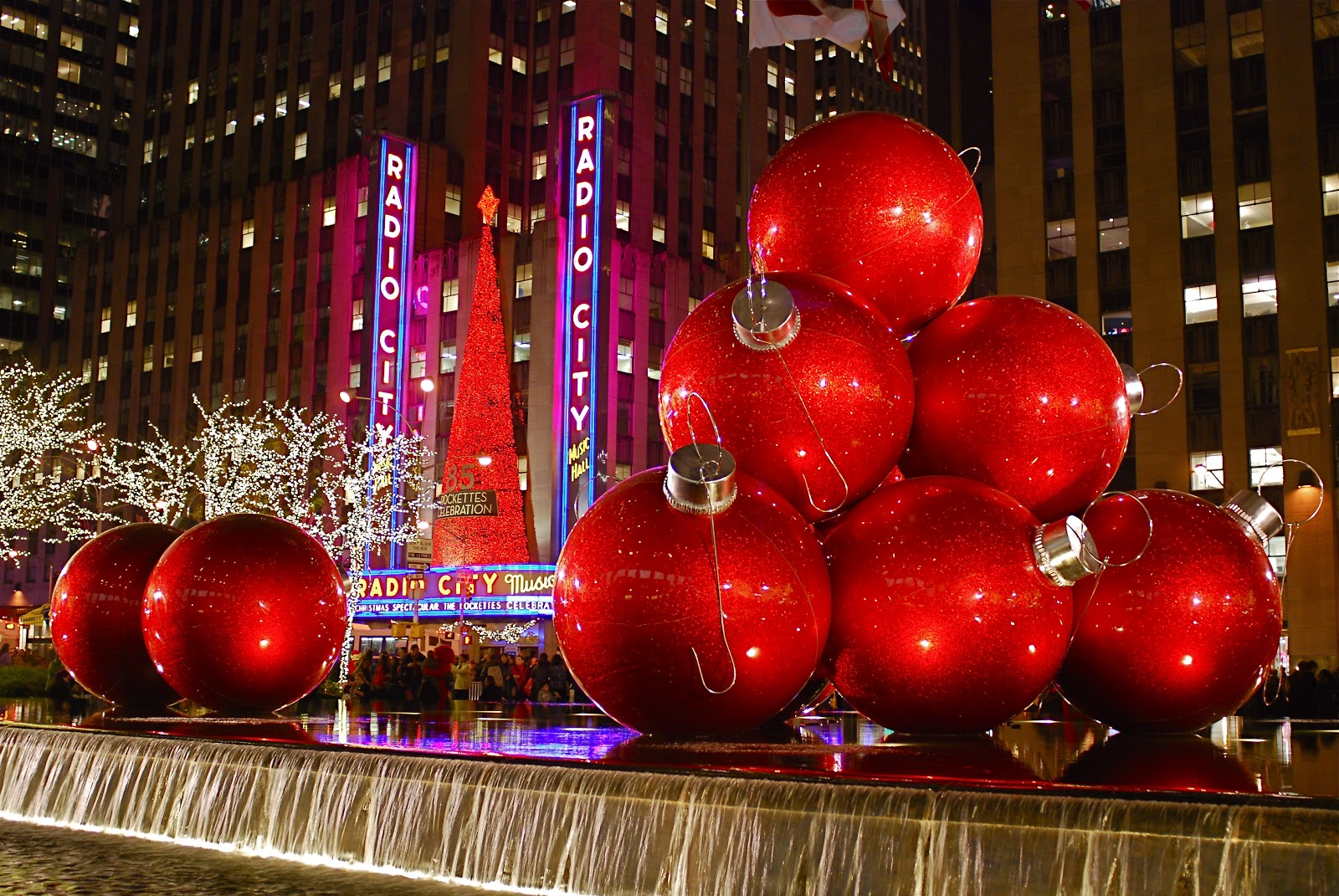 as in past years giant red christmas ornaments lights toy soldiers model train and christmas trees are on display along sixth avenue avenue of the