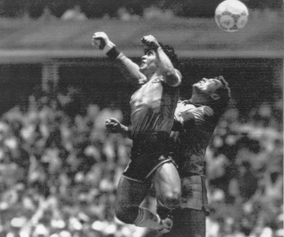 "In this June 22, 1986 file photo Argentina's Diego Maradona, left, beats England goalkeeper Peter Shilton to a high ball and scores his first of two goals in a World Cup quarterfinal soccer match, in Mexico City. On this day: This was the day of the ""Hand of God,"" when Maradona used his left fist to knock a ball past England's Shilton."