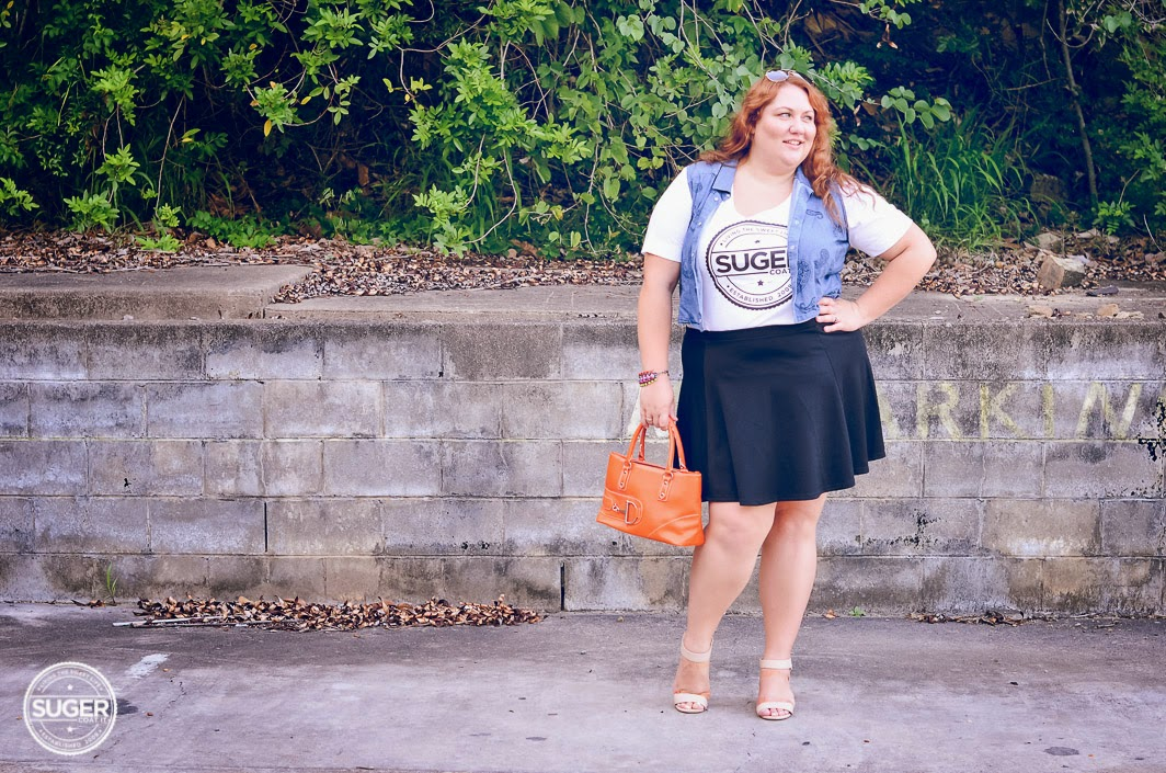 Melissa from Suger Coat It blog wearing denim vest over yellow tee and short black skirt