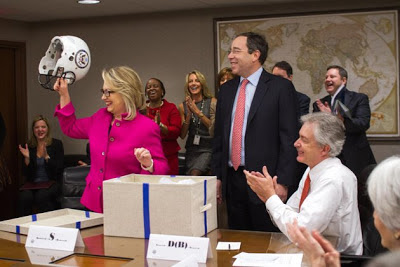 Hillary Clinton presented with football helmet on her first day back after head injury