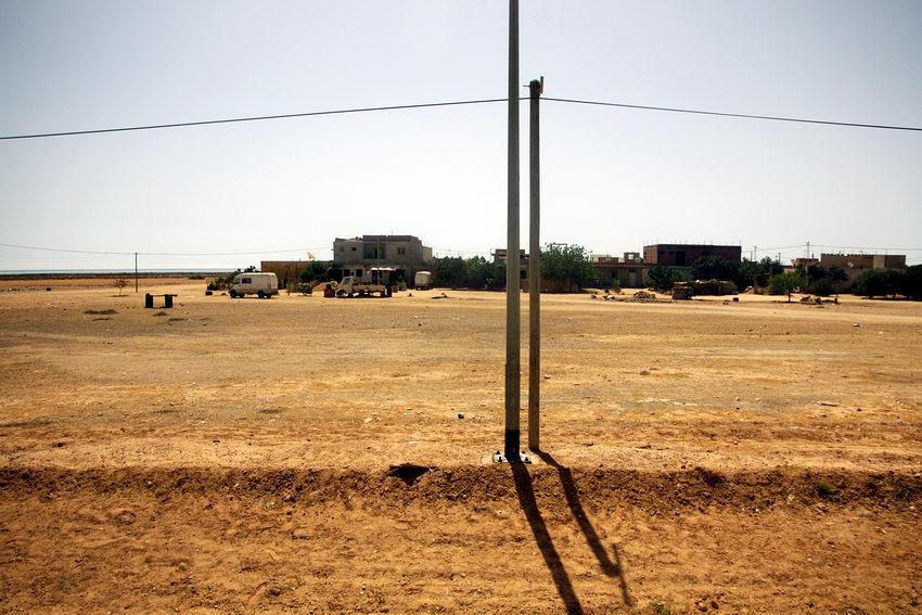 Foto de um descampado na beira da estrada, em contra-luz, com dois postes em primeiro plano. Ao fundo, algumas carrinhas junto a casas. Céu claro