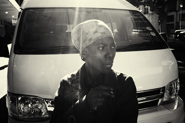 A woman smoking in front of a taxi in this street photograph shot outside Cape Town station