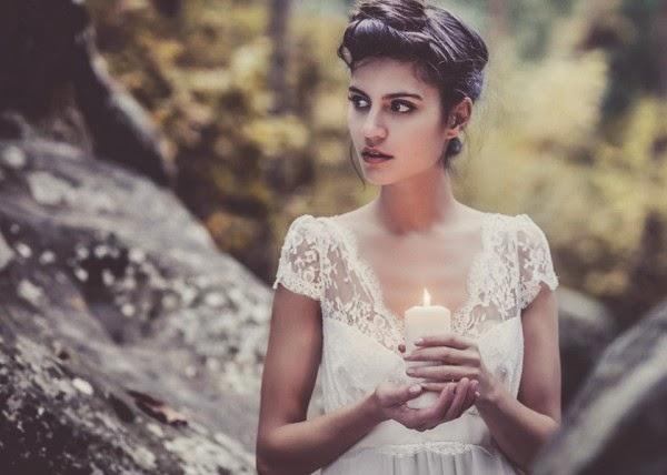 robe de mariée romantique en dentelle de calaiss femme tenant une bougie dans une foret, mystique