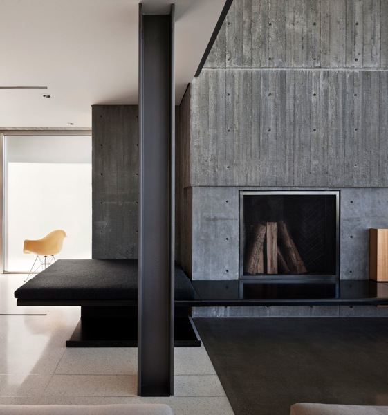 Picture of modern minimalist fireplace in the living room made of bare grey concrete