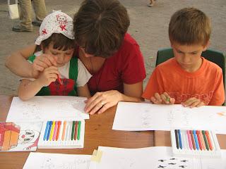 Kétéves-forma leányka ül anyja ölében és ketten rajzolnak. Mellettük egy narancssárga blúzos kisfiú összevont szemöldökkel figyeli az előtte levő játszó-feladatlapot.