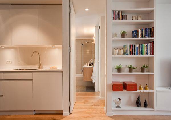 Một bên là khu vực bếp, bên kia là kệ sách và cũng là nơi lưu giữ những kỷ vật của gia chủ