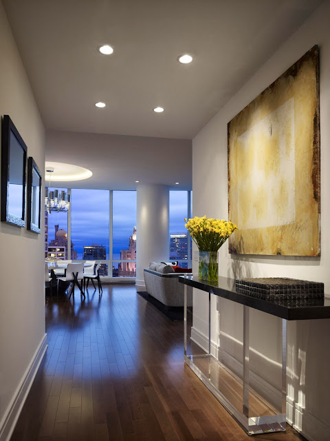 inviting entryway with abstract art and luring view by the glass windows on the end of the space