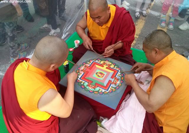Monjes tibetanos dibujando ofrenda a Buda