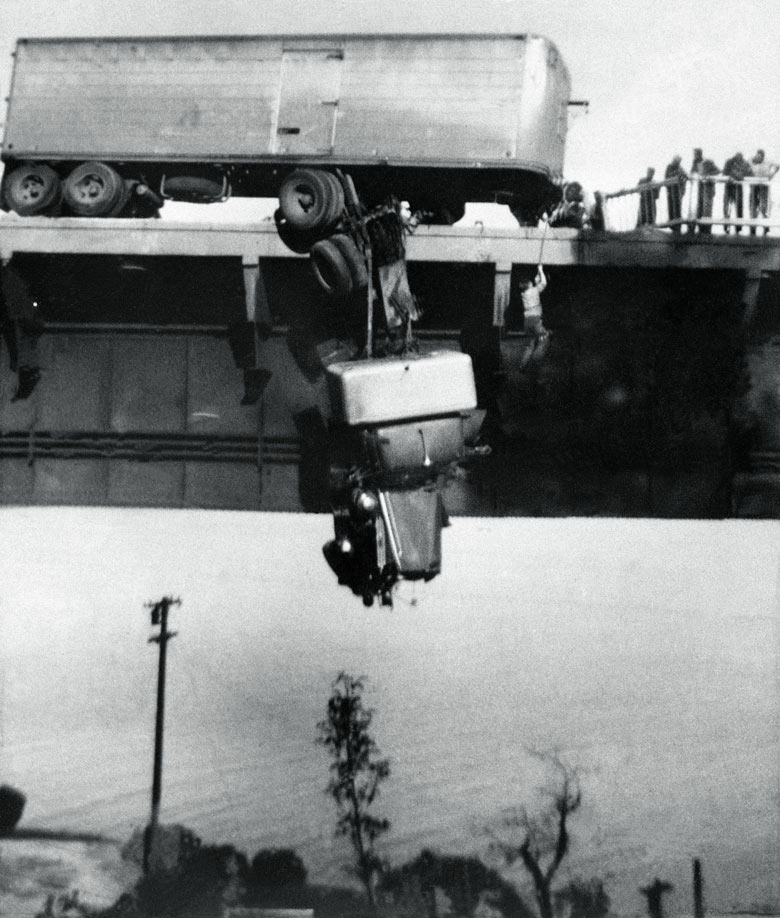 40 Amazing Historical Pictures - Paul Overby, one of two drivers trapped in the cab of a truck, is pulled to safety by a rope on the Pit River Bridge, over Shasta Lake, CA, 3 May 1953