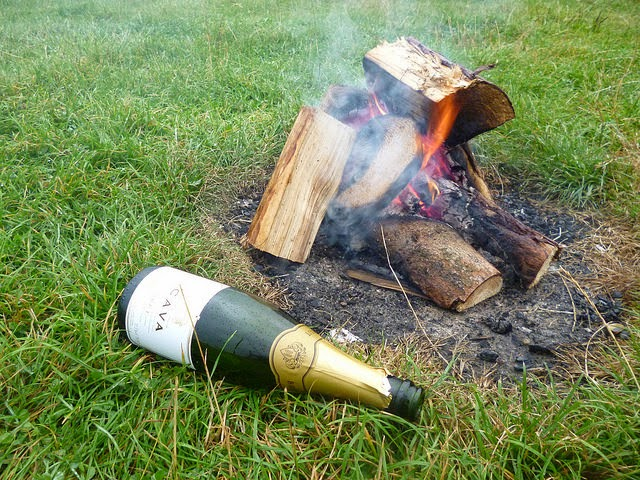 empty cava bottle by the campfire