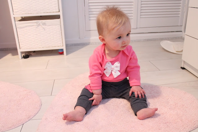 baby wearing pink bow vest from tk maxx and padded cat knee trousers from next