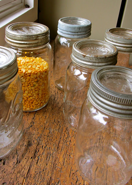 empty vintage mason jars on a counter with one full of split peas