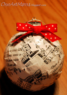 globe christmas ornament covered in sheet music with red bow