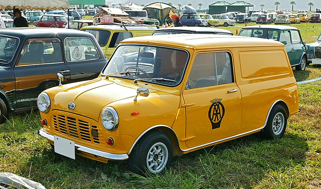 A mini Van 850 in AA original colours parked in a field in a classic car show facing left