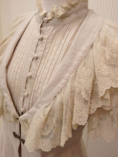 A beautiful, Victorian blouse featuring pintuck details, a high neck collar, and a lacy overshawl.