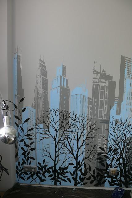 Malowanie obrazu na ścianie w sypialni przedstawiającego panoramę miasta,