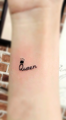 A word queen tattoo with a crown on the letter Q