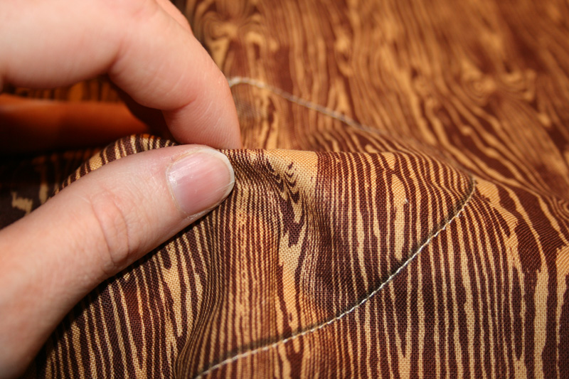 pull the wood grain fabric away from the backing and cut the fabric away to expose the embellished backing