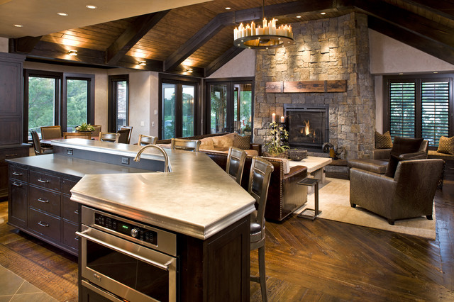 Cozy Family Room with Rounded Chandelier and Stone Rustic Fireplace Mantels near Brown Sofas and Low Table