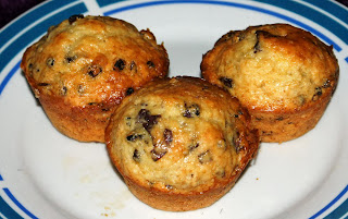 three cornmeal and flour muffins incorporating hibiscus flowers and mulberries made without butter presented on a plate