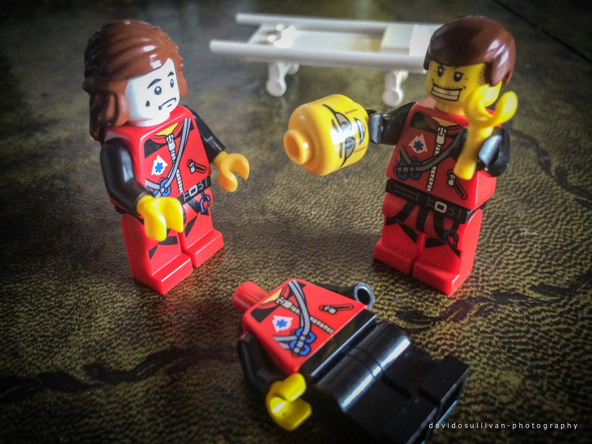 Three Lego figures, One laying down, One Worried and one holding the first's head and hand
