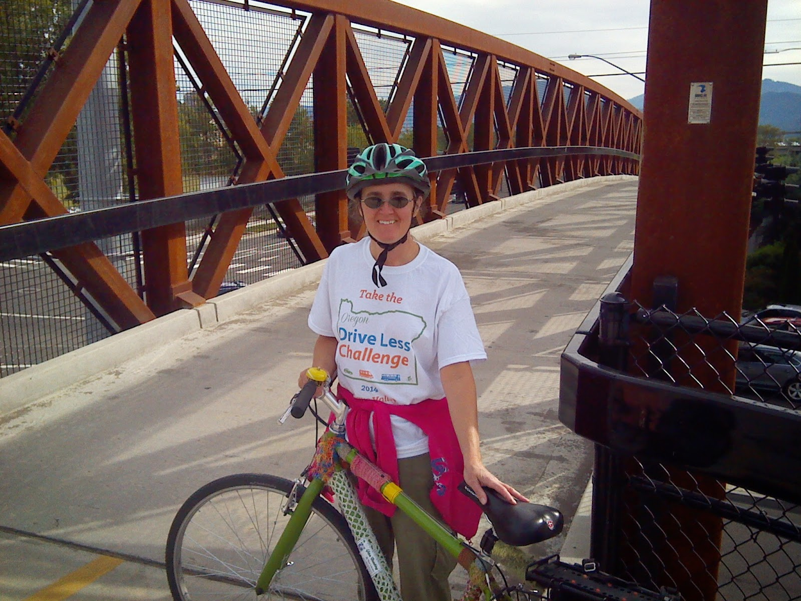 Cynthia M. Parkhill with her bicycle on a pedestrian walkway over a road.