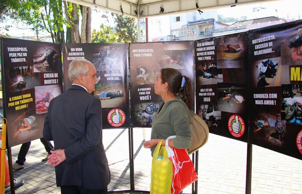 População visita a exposição de fotografias com vítimas reais de acidentes no trânsito montada na Praça da Matriz de Santa Teresa