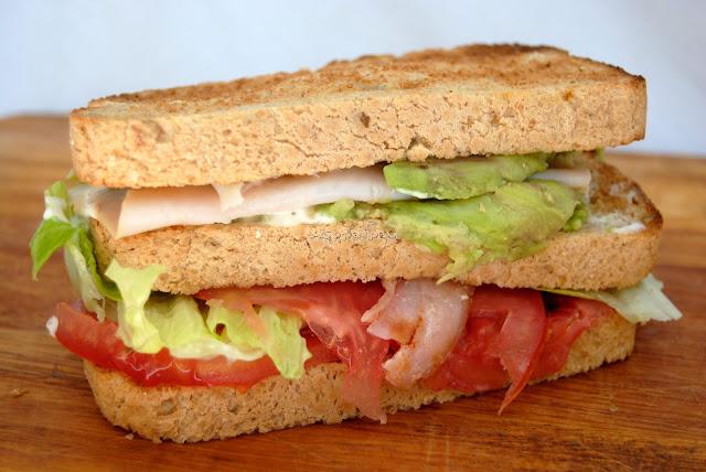 Sándwich casero con lechuga, tomate, pavo, bacon crujiente y aguacate