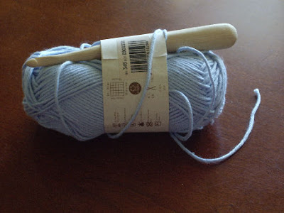 photo of a chunky wooden crochet hook tucked into a ball of yarn.