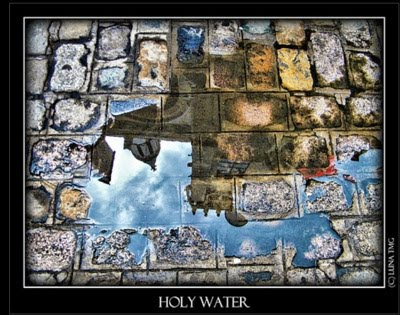 Holy Water &#8211; a church reflected in a puddle on a cobblestone street