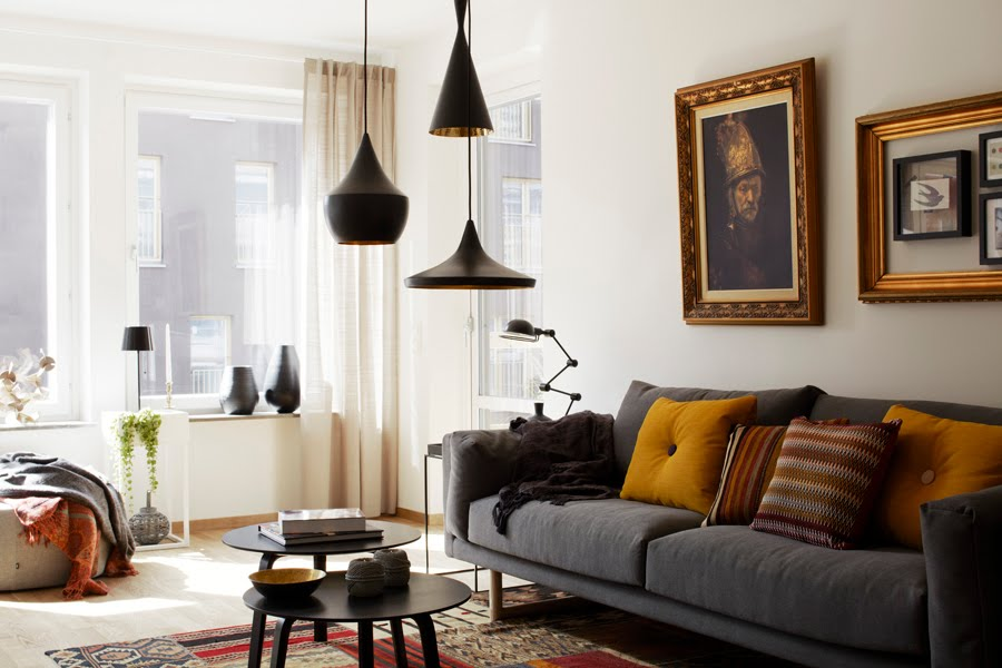 cluster of black pendant lamps over two coffee tables with a grey sofa ...