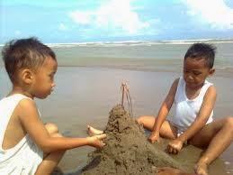 anak laki-laki bermain pasir dengan asyik di pantai