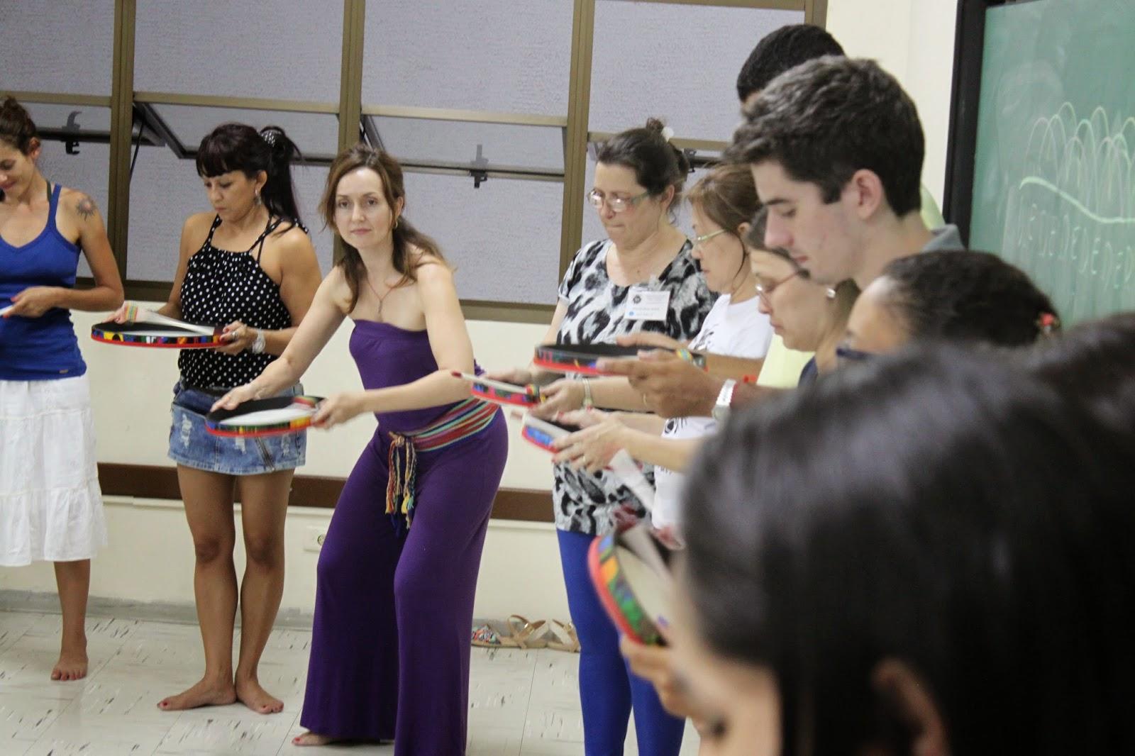Descrição da Foto: Participantes estão de pé segurando o tambor e balançando como uma peneira.