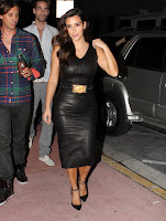 Kim Kardashian shows off her curvy body in a tight leather dress