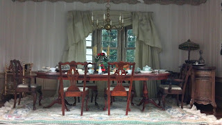 miniature dining room with chairs and table as part of a doll house