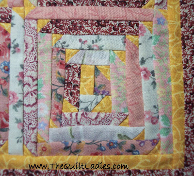 Pink Log cabin quilt with triangle corners