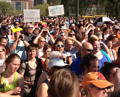 Crowd in front of the Minnesota State Capitol, including two people holding signs that say Still Waiting in Wisconsin