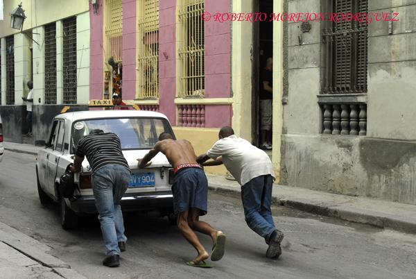 Hombres empujando un carro marca Lada que hace servicio de taxi en La Habana