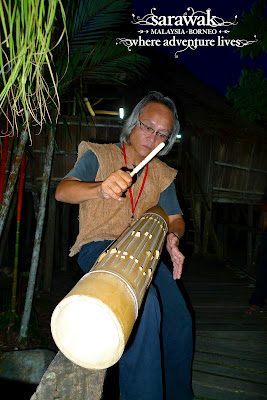 A bidayuh playing his pratuakng, a bamboo percussion musical instrument