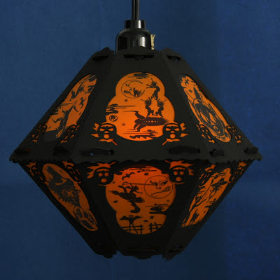 Silhouettes of black on orange in retro kitsch Halloween lantern in a vintage style by Bindlegrim