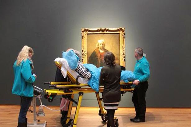 An elderly, infirm woman on a stretcher in an art gallery looking at Rembrandt painting