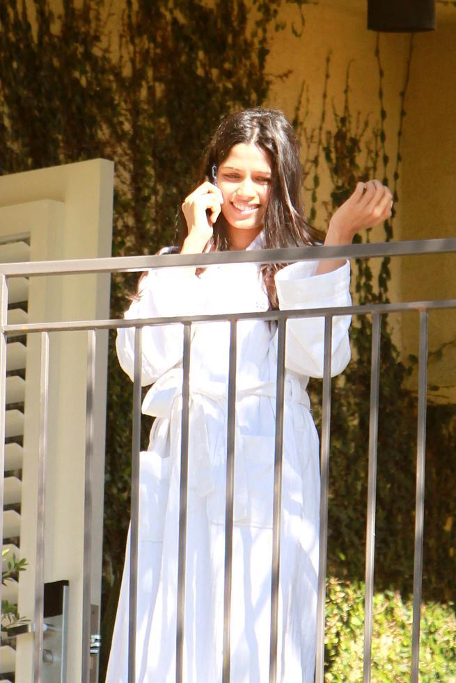 Freida Pinto in a bathing robe on hotel balcony