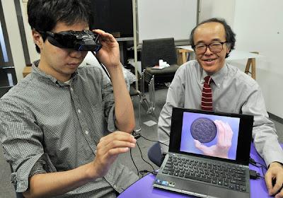 HIROSE (kanan) duduk di sebelah seorang penyelidik yang melihat biskut kecil yang dipegangnya kelihatan besar menerusi gogal yang dipakainya di sebuah makmal di Tokyo pada Sabtu lalu.