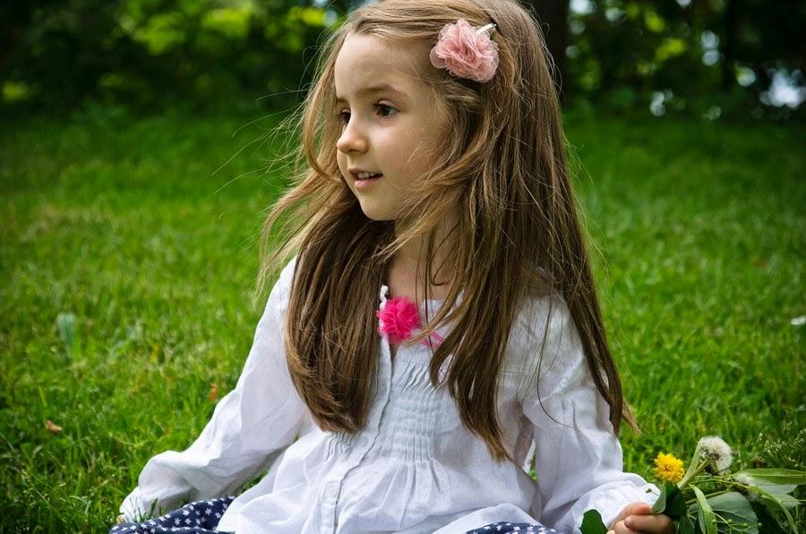 Gambar bayi perempuan bermain dengan bunga wallpaper gratis