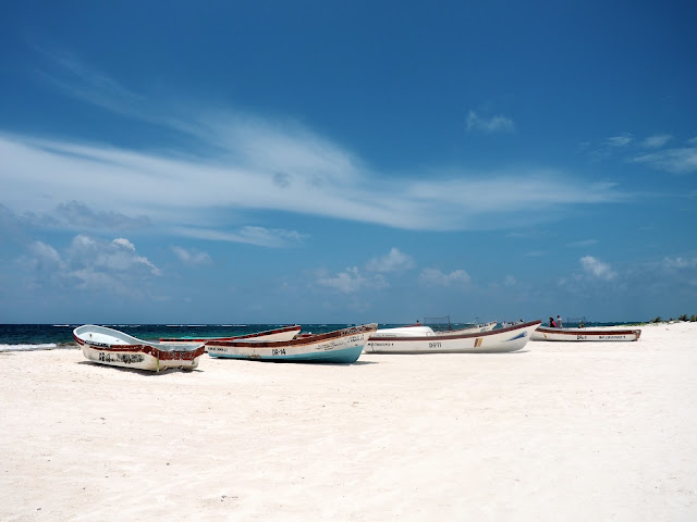 Small fishing boats on the white sand of Tulum beach, Mexico