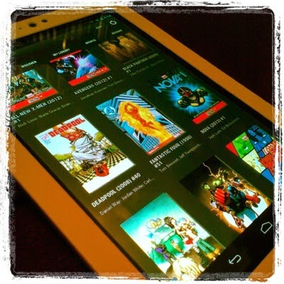 An e-reader with a number of comics covers displayed in rows on its screen. The titles are described below.