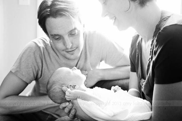 parents looking lovingly at newborn